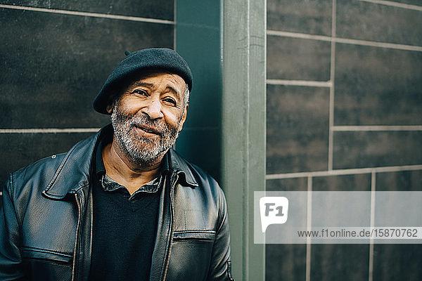 Lächelnder älterer Mann an der Wand