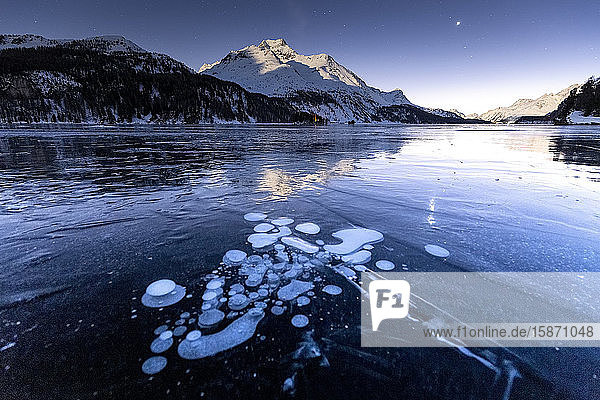 Methane bubbles in the icy surface of the lake with snowy peak illuminated by moonlight  Sils  Engadine Valley  Graubunden  Swiss Alps  Switzerland  Europe