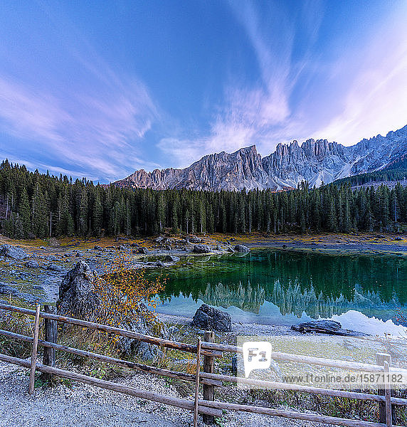 Dramatic sky at sunset over Carezza Lake and Latemar peaks in autumn  Dolomites  South Tyrol  Italy  Europe