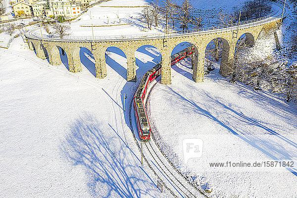 Bernina Express passes under the helical (spiral) viaduct of Brusio  UNESCO World Heritage Site  Valposchiavo  Canton of Graubunden  Switzerland  Europe