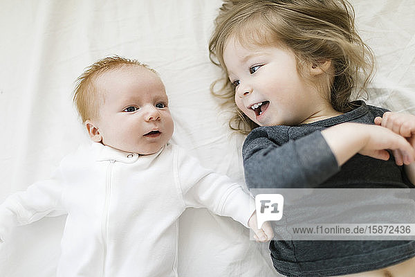 Siblings (2-5 months  2-3) lying on bed