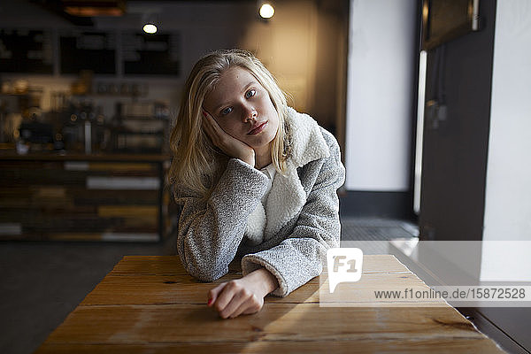Young woman sitting at cafe table