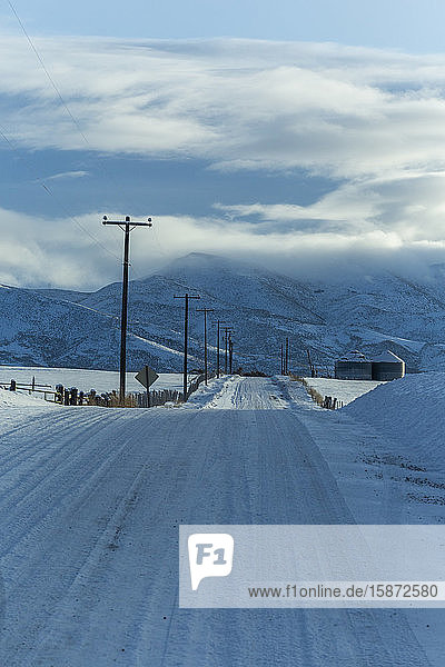 Snowy road with mountains in distance