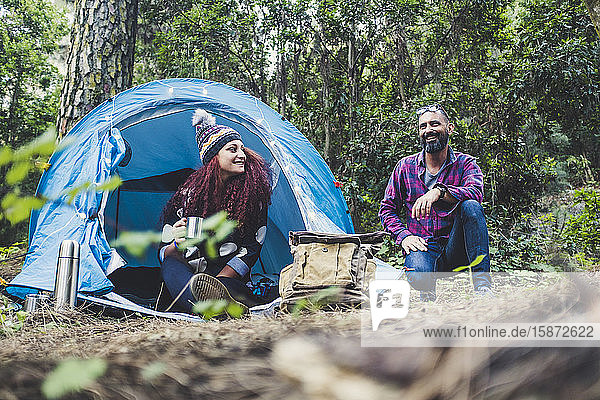 Smiling couple sitting by tent