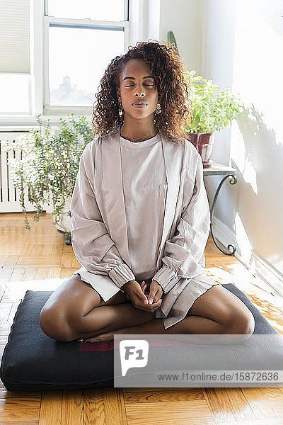 Woman meditating on cushion Woman meditating on cushion