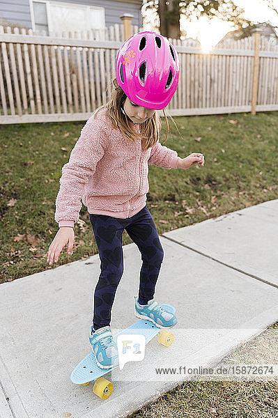 Girl skateboarding down a sidewalk