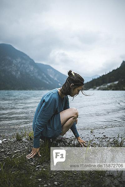 Young woman crouching by lake Young woman crouching by lake