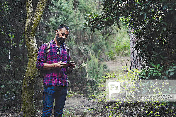 Man using smart phone in forest Man using smart phone in forest