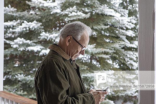 Senior man using smart phone by snowy tree Senior man using smart phone by snowy tree