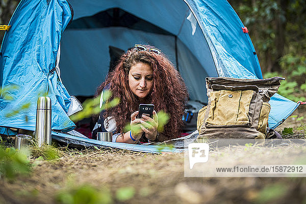 Woman lying in tent using smart phone