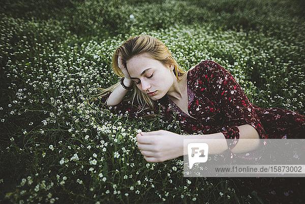 Woman wearing dress lying in meadow