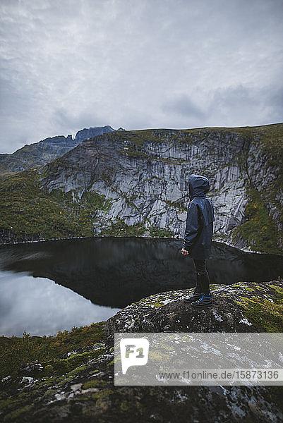 Man standing on rock by lake in Lofoten Islands  Norway Man standing on rock by lake in Lofoten Islands, Norway