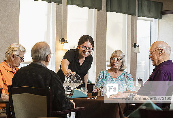 Smiling waitress pouring water for senior people