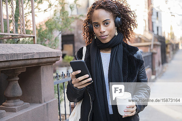 Woman wearing headphones holding smart phone and cup Woman wearing headphones holding smart phone and cup