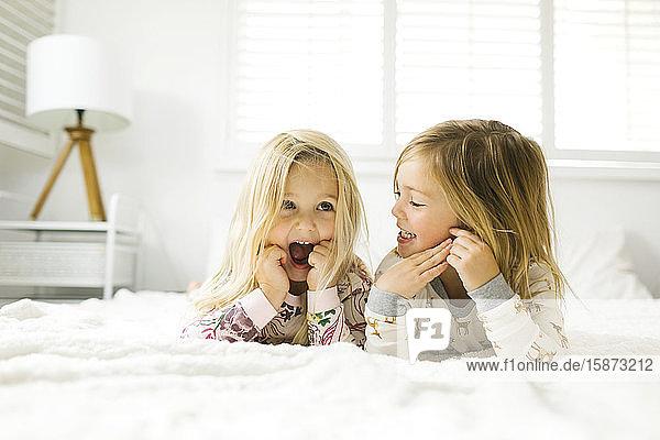 Sisters lying on bed Sisters lying on bed