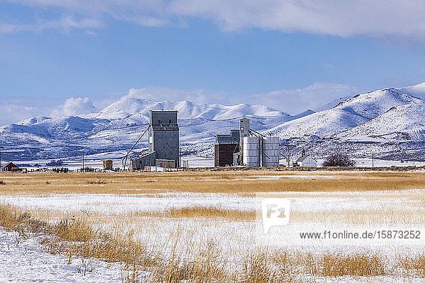 Farm in snowy field by mountains Farm in snowy field by mountains