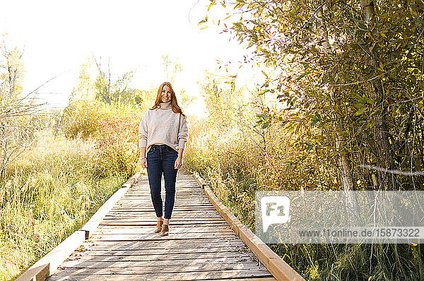 Smiling woman standing on forest boardwalk Smiling woman standing on forest boardwalk