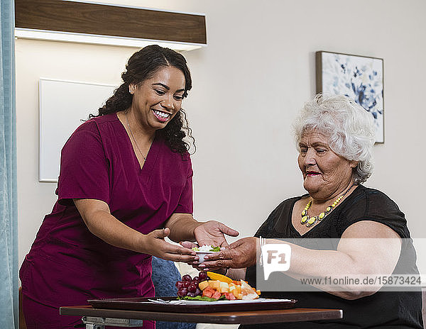 Smiling nurse handing food to senior woman