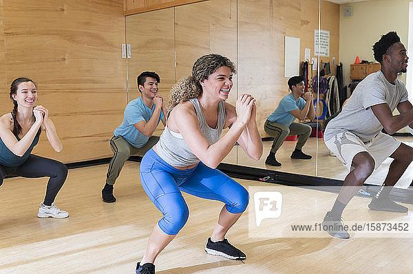 Men and women exercising in workout class Men and women exercising in workout class