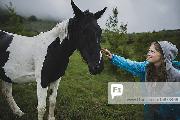 Smiling woman petting Icelandic horse