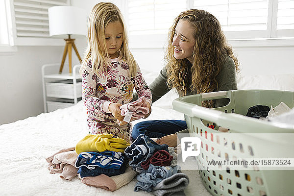 Mother and daughter folding laundry on bed