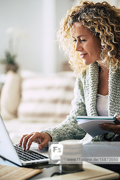 Smiling woman working with laptop on sofa Smiling woman working with laptop on sofa
