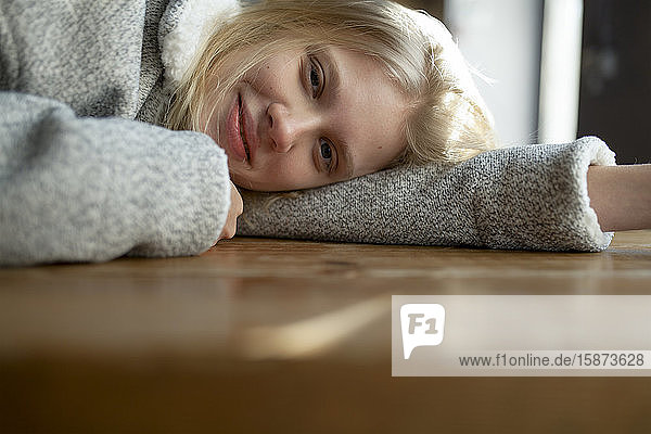 Young woman in wool coat lying on cafe table