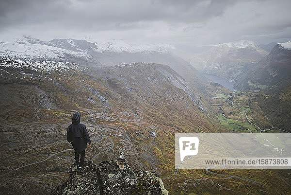 Man standing on Dalsnibba mountain overlooking valley in Geiranger  Norway Man standing on Dalsnibba mountain overlooking valley in Geiranger, Norway