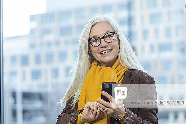 Smiling businesswoman with smartphone in office Smiling businesswoman with smartphone in office