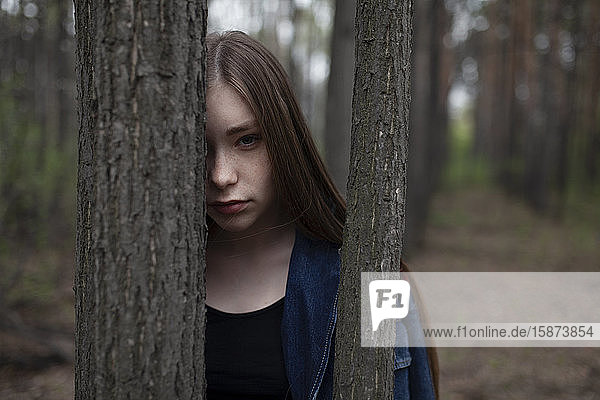 Young woman behind tree trunks in forest