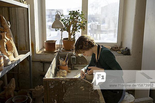 Potter working at desk in workshop Potter working at desk in workshop