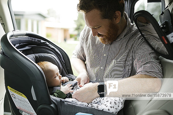 Father buckling baby boy (2-3 months) in car seat Father buckling baby boy (2-3 months) in car seat