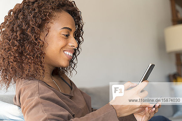 Smiling woman holding credit card and smart phone Smiling woman holding credit card and smart phone