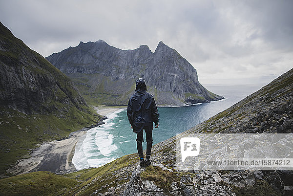 Man standing on rock by Kvalvika Beach in Lofoten Islands  Norway