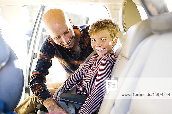 Boy smiling as his father buckles his seat belt Boy smiling as his father buckles his seat belt