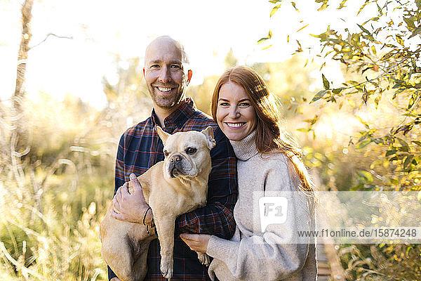 Lächelndes Paar mit französischer Bulldogge im Wald