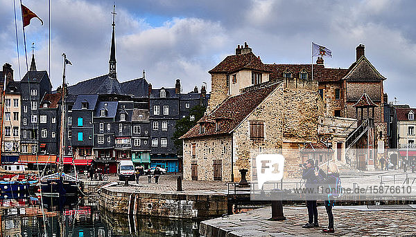 photographer Honfleur  Calvados  Normandie  France. Honfleur is located on the estuary of the River Seine  near the famous Normandy Bridge Honfleur is famous for its picturesque port  including colorful buildings and houses with slate-covered frontages. The port of Honfleur was painted many times by artists which gave birth to the impressionist movements : Claude Monet  Gustave Courbet and Eugène Boudin.