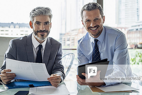 Smiling businessmen holding document and digital tablet
