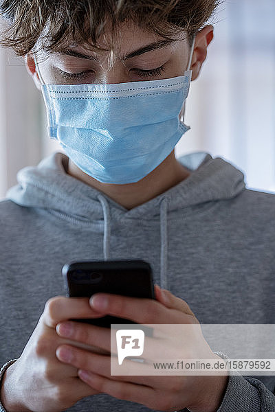 Close up of teenage boy with medical mask using smartphone during coronavirus
