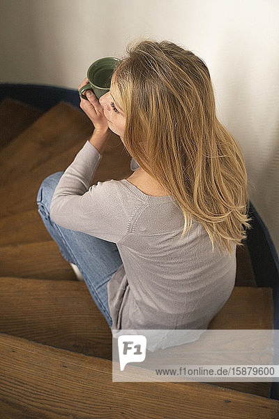 Young woman holding cup while sitting on steps