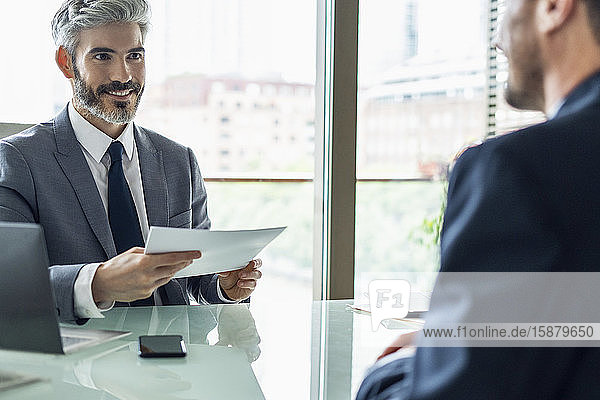Smiling businessman holding document in office