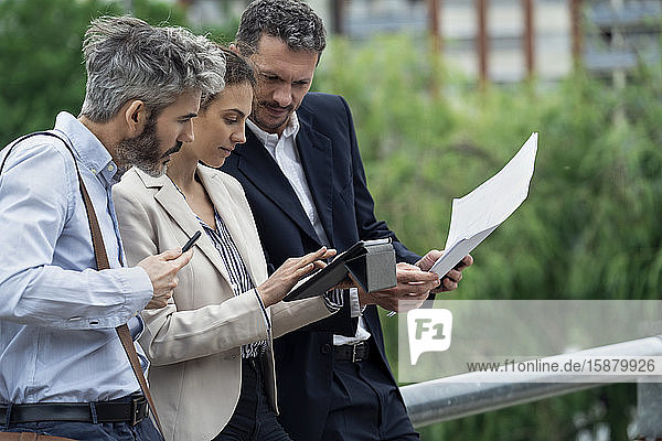 Architects using digital tablet outdoors