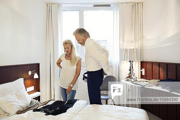 Ein Paar steht in einem Hotelzimmer und betrachtet die auf dem Bett ausgelegten Kleider.