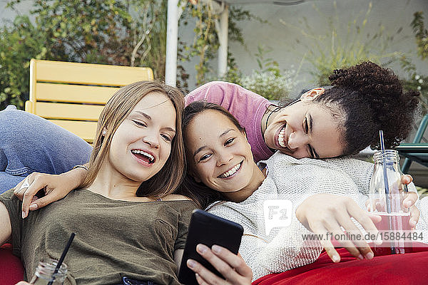 Three women lounging together  laughing and looking at a mobile phone.