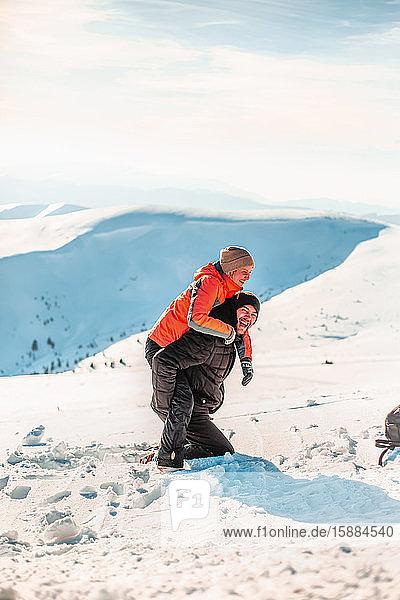 Ein Mann in einem Skianzug  der im Schnee kniet und einer Frau einen Huckepack gibt  lacht und schaut in die Kamera.