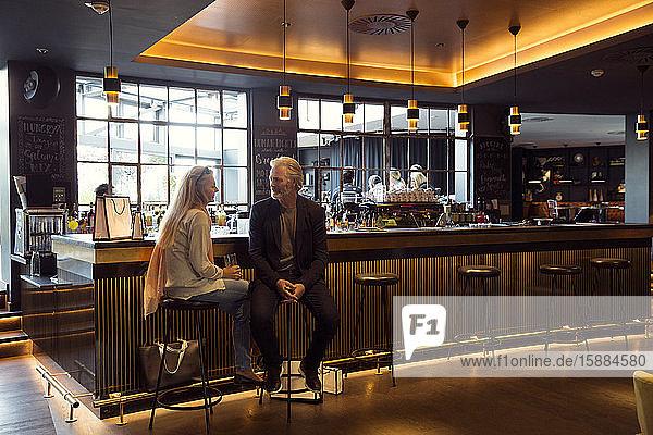 Ein Paar  das auf Barhockern neben einer Bar sitzt.