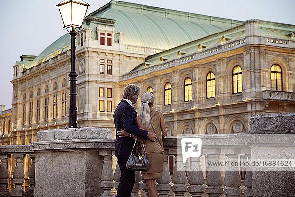 Rückansicht eines Paares  das über eine Balustrade an einer Wiener Straße blickt.