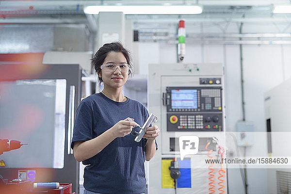 Ingenieurin  die in der Fabrik neben einer CNC-Drehmaschine steht und in die Kamera schaut.