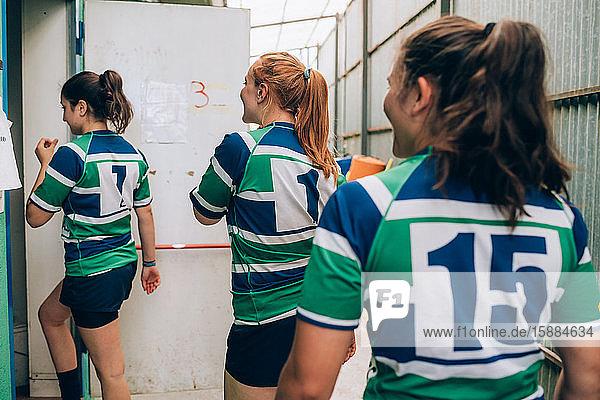 Rückansicht von drei Frauen in blauem  weißem und grünem Rugby  die durch eine Tür in ein Gebäude gehen.
