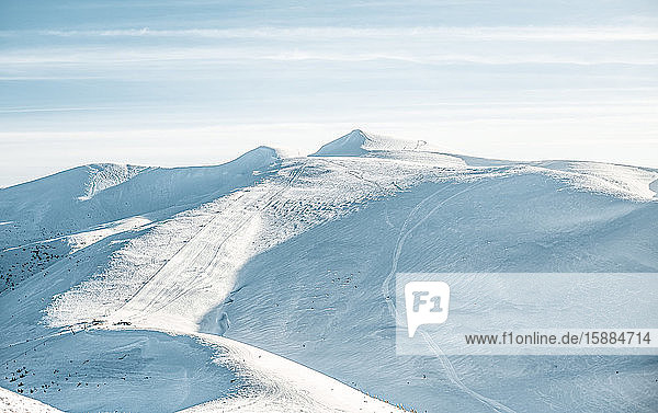 View of deserted ski slopes in the mountains  empty pistes with snow tracks.